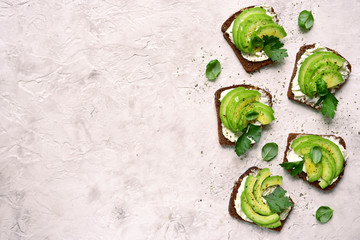 Rye avocado toasts with ricotta cheese.Top view with copy space.