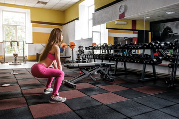 girl doing squats in the gym