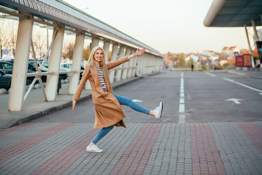 Full height of playful funny blond elegant woman in beige coat crossing the street at a pedestrian crossing.