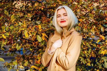 Attractive blonde woman with red lips in beige coat over yellow tree in sunny autumn day.