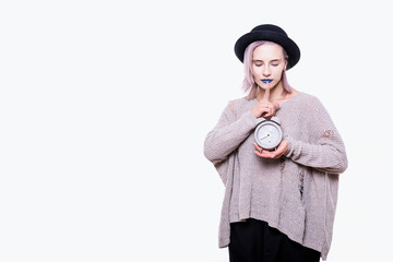 Portrait of young emotional attractive woman in black hat, torn sweater, with blue lips and pink hair, she is holding grey alarm clock, isolated on white background with copy space.