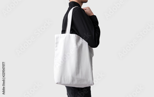 Man Is Holding Bag Canvas Fabric For Mockup Blank Template Isolated On Gray Background