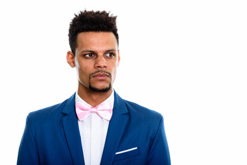 Studio shot of young African businessman thinking while looking
