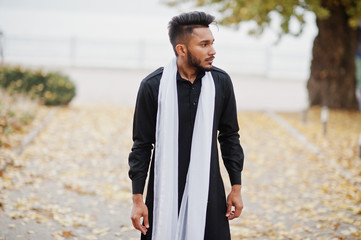 Indian stylish man in black traditional clothes with white scarf posed outdoor against autumn leaves tree.