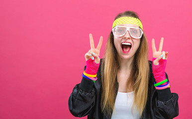 Woman in 1980's fashion giving the peace sign on a pink background