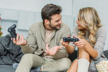 happy young couple playing video games together on couch at home
