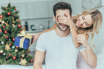 beautiful young woman presenting christmas surprise gift to boyfriend in bed at home