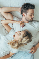 top view of beautiful young couple sleeping together in bed at home