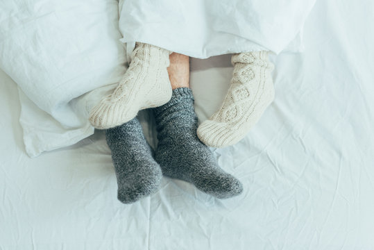 cropped shot of couple in woolen socks lying in bed together at home
