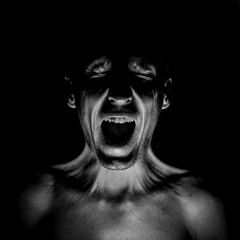 Stylish dark portrait of screaming adult caucasian man. Fear concept. Black and white shot, low key lighting.