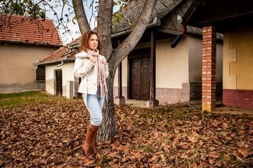 Beautiful curly woman standing next to a tree on brown leaves during autumn on a vineyard