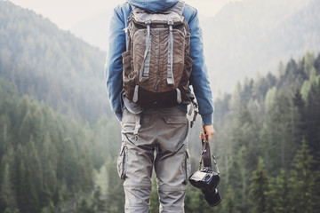Young cheerful man photographer holding digital camera in a mountains. Taking pictures. Photography, travel and active lifestyle concept