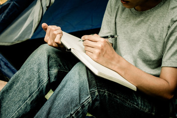 Asian young man sitting is holding a pen writing note of  letter memorize memories on book  in outside the tent. Loneliness camping in forest