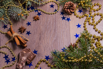 Light wooden background with Christmas trees tinsel beads and New Year's decor