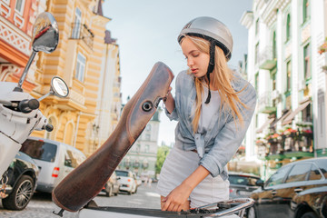 Smart and good-looking girl is looking under motorcycle seat. She is looking for something. Girl is stnding outside on street.