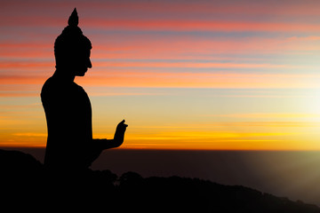 Silhouette of Buddha statue on sunrise background