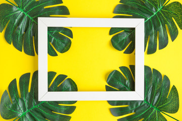 Flat lay abstract of picture frame and monstera leaves isolated on yellow.