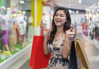 cheerful woman with shopping bags in mall