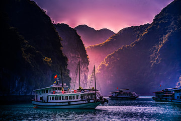 Stunning image of tourist cruise ship among green rocks in sunset light on Halong Bay, Vietnam