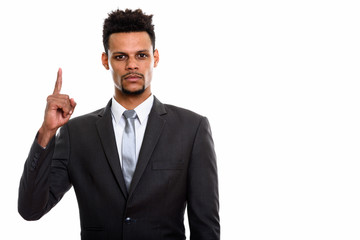 Studio shot of young African businessman pointing finger up