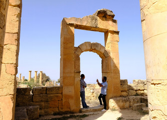 A man takes a picture of his friend in the ancient ruins of the Greek and Roman city of Cyrene, in Shahhat