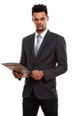 Studio shot of young African businessman holding clipboard