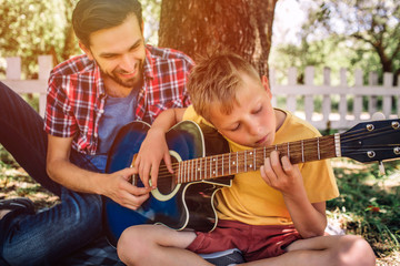 Talented boy is looking on strings and playing guitar. His father is sitting besides him and helping him. Adult is smiling.