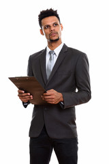Young African businessman holding clipboard while thinking and l