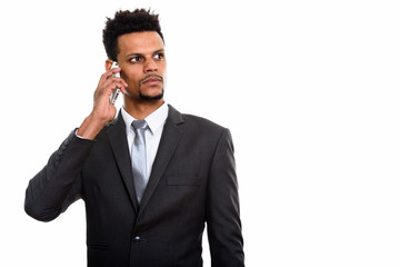 Young African businessman talking on mobile phone while thinking