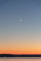Crescent moon over horizon puget sound