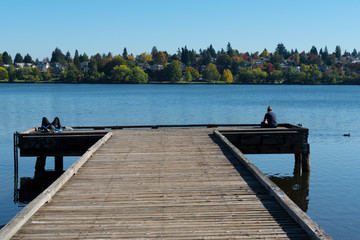 Two people on opposite ends of a lake dock in autumn