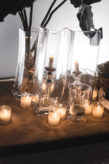 Decorated table for a cocktail at night with candles, jars and plants