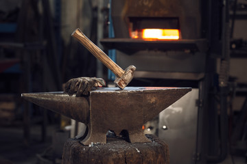 Mallet and gloves on an anvil in front of a furnace