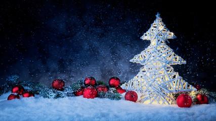 Leuchtender Weihnachtsbaum mit Weihnachtskugeln und Tannenzweig vor dunklem Hinterdrund mit Schnee