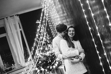 A guy with a girl is celebrating Christmas. A loving couple enjoy each other on New Year's Eve. New Year's love story. Man and woman enjoy the moment and playing with garlands.