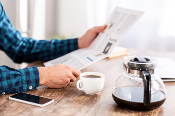 cropped shot of man in checkered shirt reading newspaper and drinking coffee at home