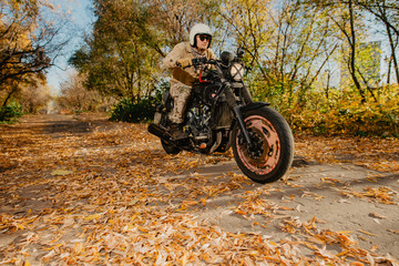 young man on a motorcycle rides through an autumn alley with leaves
