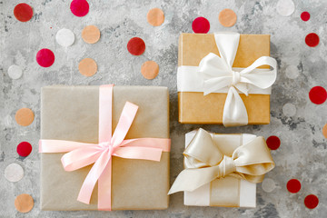 Festive composition with beautiful presents wrapped in craft paper and tied with a ribbon, multiple colorfull round shaped confetti on background. Close up, copy space, top view, flat lay.