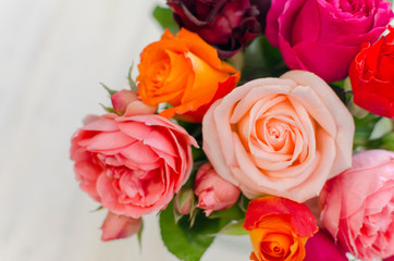 Valentines day background with colorful fresh roses laying on white table.