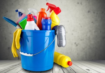 Cleaning products in bucket on background