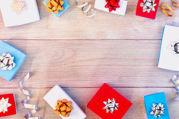 Small white, red and blue gift boxes, ribbons and bows. Christmas composition, frame. In the center there is a place for text, copy space.