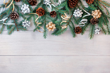 Composition of fir branches, decorative ribbons, bows and cones on a light wooden background. Copy space. Festive Christmas layout.