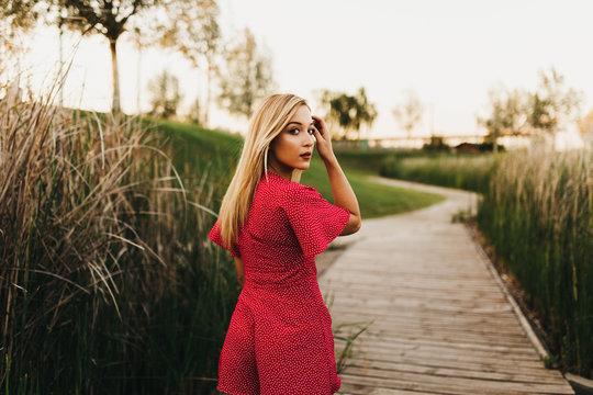 Woman in red dress on footbridge