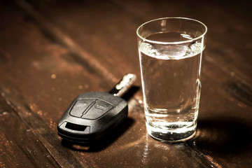 The concept of driving under the influence of alcohol - car keys, a glass of alcohol