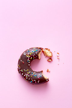 Half eaten donut with chocolate coating and sprinkles on a pink background viewed from above. Sweet food leftovers. Top view. Copy space