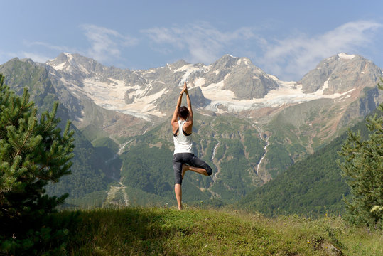 Young athletic woman doing yoga on the background of snow-capped mountains.