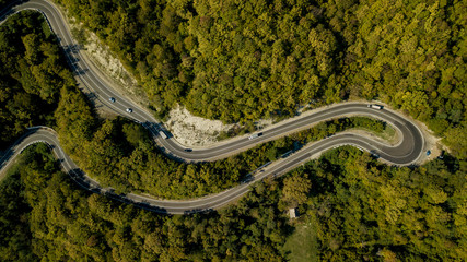 Directly above view of cars on a curvy road. Aerial drone shoot in the mountains.