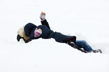 Two young girls having fun in winter and lying in the snow
