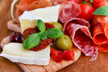 Foto op Aluminium Assortiment Traditional italian antipasto with prosciutto, parmesan cheese and brie cheese, sun-dried tomatoes, salami, green olives and Basil, wooden table, Italian restaurant, selective focus