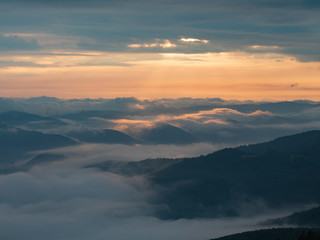 Landscape of mountains, clouds and sun going west. Carpathians mountains in august, west Ukraine. Nature background. Sun illuminating white clouds in the evening. Blurred background